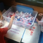 For our Patriotic 4th of July Sensory Tub we used some patriotic paper, cut into strips, as well as some stars and red, white and blue pompoms.